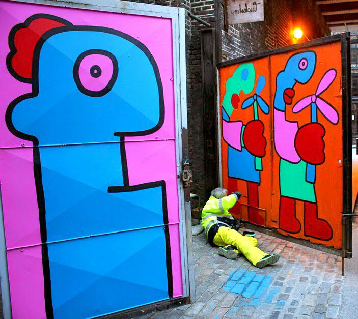 Street artist Thierry Noir attempts to put some colour into Londoners' life offering them flowers.