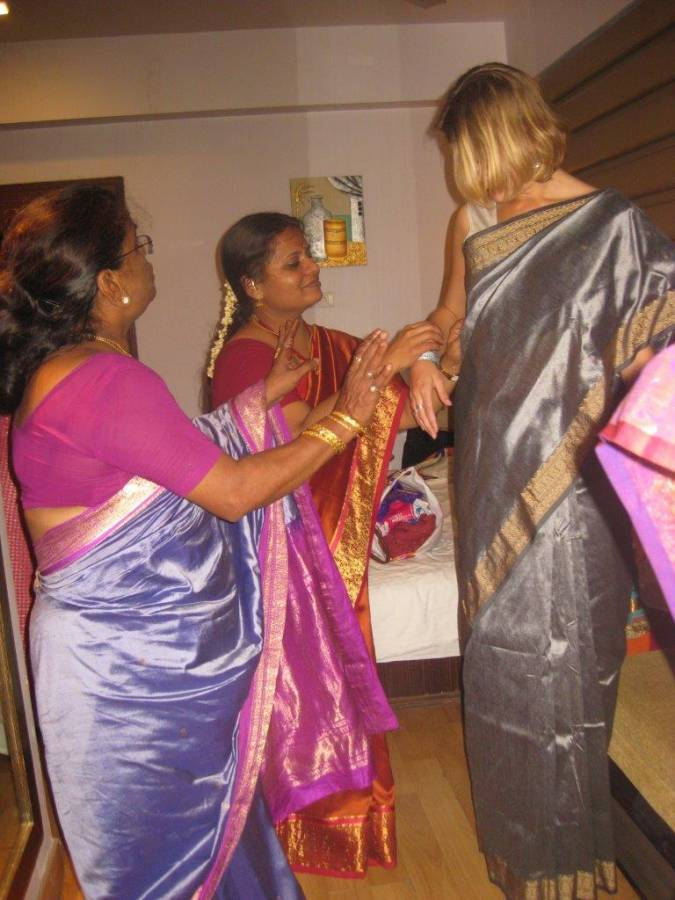 While working for a publishing company in Pune, India I was invited to an Indian wedding in Mumbai. In this picture family of the bride is helping me into a traditional Sari, bought for the occasion.
