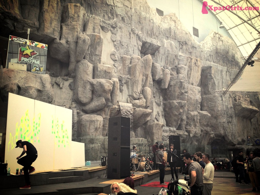 A small rock concert and graffiti painting inside a mall