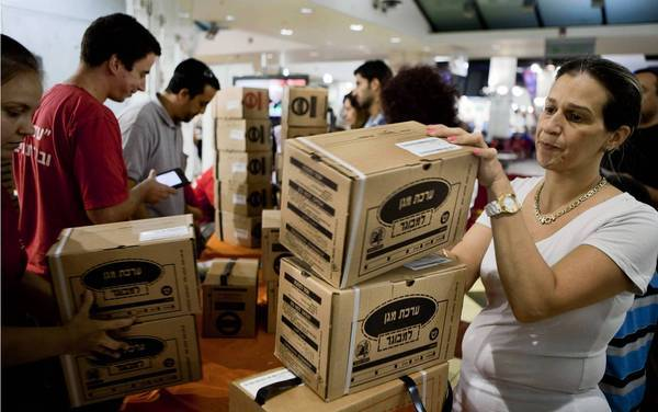 An Israeli woman collecting her family's gas masks kits at a distribution center in a mall